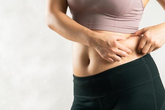 Mulher gorda, barriga gorda, gordinha, mulher obesa mão segurando a gordura da barriga excessiva
