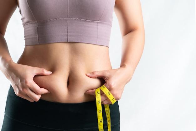 Mulher gorda, barriga gorda, gordinha, mulher obesa mão segurando excesso de gordura da barriga com fita métrica