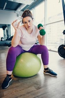 Mulher gorda cansada fazendo exercícios com halteres enquanto está sentada na bola de ginástica no ginásio
