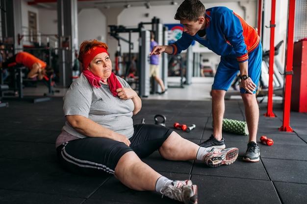 Mulher gorda cansada se senta no chão, treino com instrutor na academia. queima de calorias, mulher obesa em clube esportivo