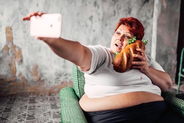 Mulher gorda com sanduíche na mão faz selfie, preguiça e obesidade, pessoas com excesso de peso. estilo de vida pouco saudável, mulher gorda