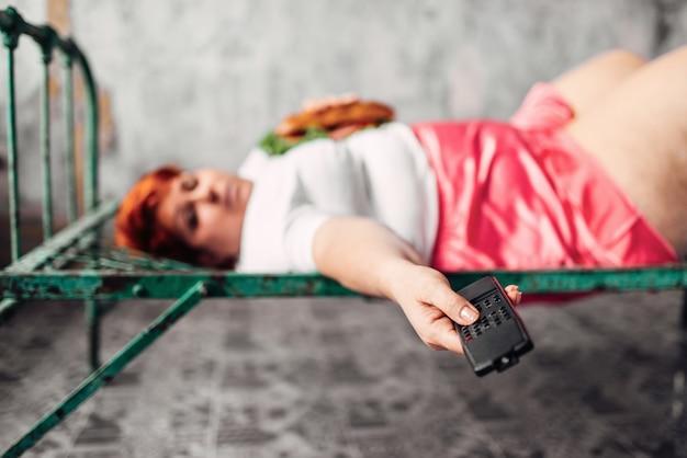 Mulher gorda com sanduíche nas mãos deitada na cama e assiste tv, preguiça, bulímica e com sobrepeso. estilo de vida pouco saudável, obesidade