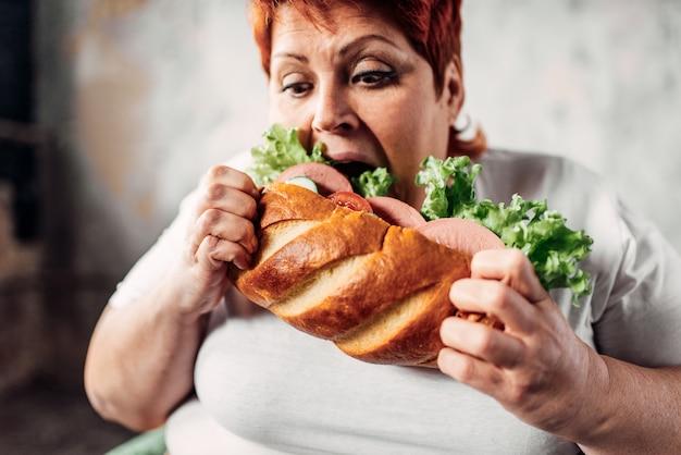 Mulher gorda come sanduíche, com sobrepeso e bulímica. estilo de vida pouco saudável, obesidade