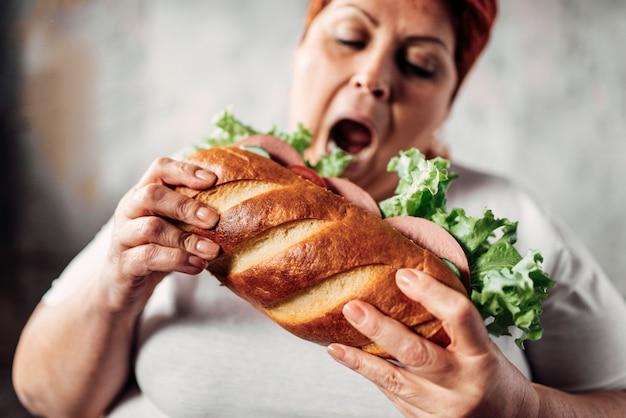 Mulher gorda come sanduíche, com sobrepeso e bulímica