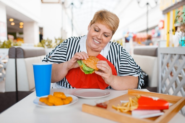 Mulher gorda comendo fastfood na praça de alimentação do shopping.