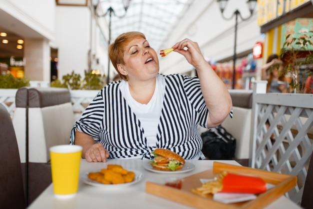 Mulher gorda comendo hambúrguer na praça de alimentação do shopping.