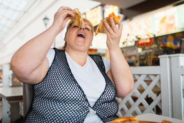 Mulher gorda comendo pizza em restaurante de shopping, comida pouco saudável. mulher com sobrepeso à mesa com jantar junk, problema de obesidade