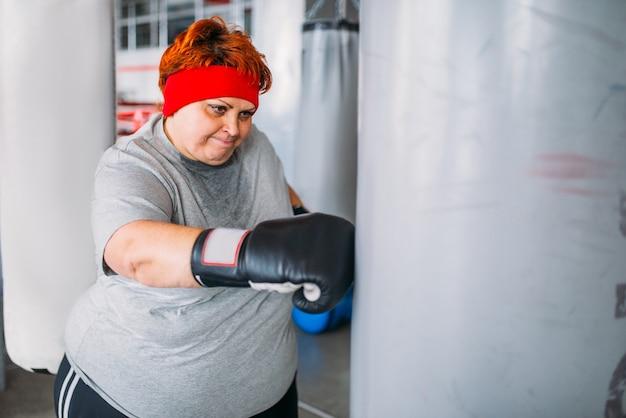 Mulher gorda em luvas de boxe trabalha com saco de pancadas, treino no ginásio.