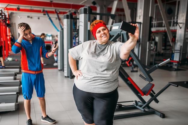 Mulher gorda fazendo selfie com instrutor na academia