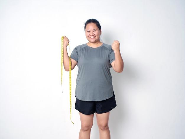 Mulher gorda feliz com fita métrica em fundo branco