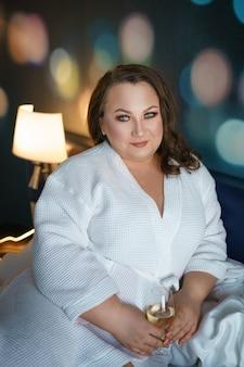 Mulher gorda grande no roupão branco deitado na cama, relaxar no hotel