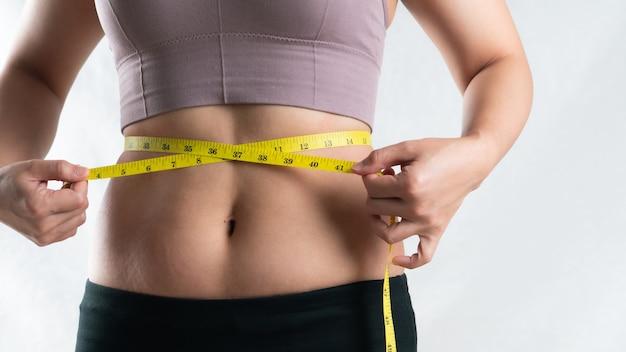 Mulher gorda, mão segurando fita métrica na barriga