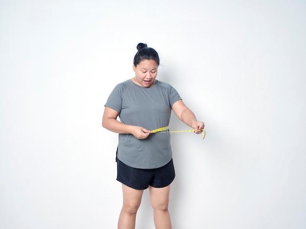 Mulher gorda medindo a cintura com fita adesiva no fundo branco
