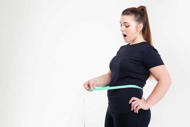 Mulher gorda medindo a cintura isolada em uma parede branca