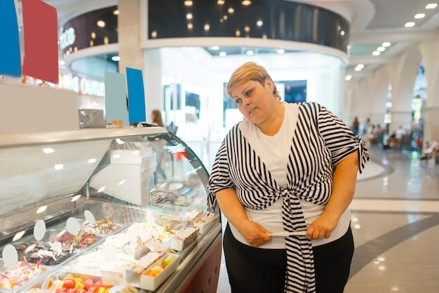 Mulher gorda na vitrine do restaurante de fast food. mulher com sobrepeso comprando fastfood, problema de obesidade