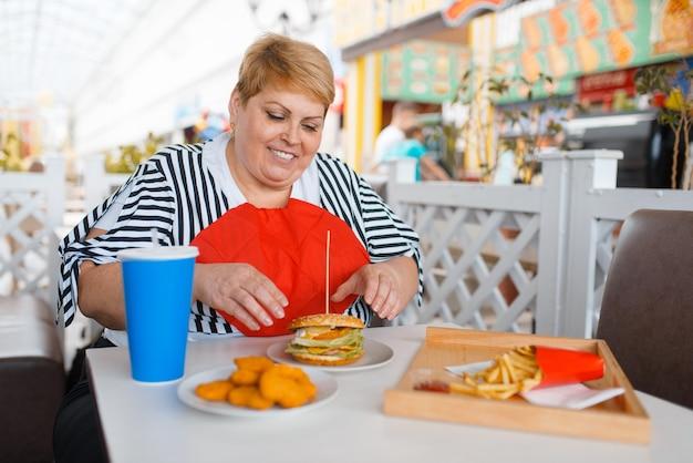 Mulher gorda se prepara para comer fastfood na praça de alimentação do shopping.