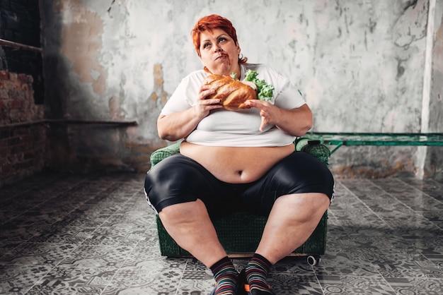 Mulher gorda se senta em uma cadeira e come sanduíche, bulímica e com sobrepeso. estilo de vida pouco saudável, obesidade