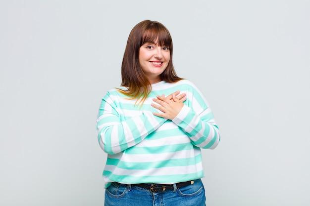 Mulher gorda se sentindo romântica, feliz e apaixonada, sorrindo alegremente e segurando o coração de mãos dadas