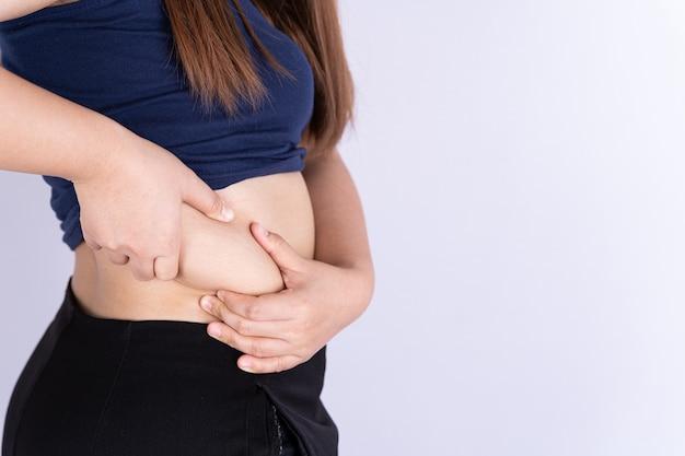 Mulher gorda segurando fundo cinza excessivo de barriga gorda isolada.