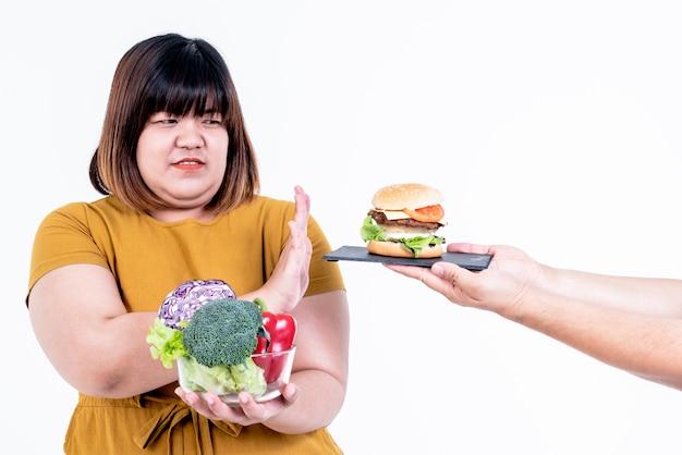 Mulher gorda segure uma tigela, muitos legumes frescos na mão e rejeite os hambúrgueres