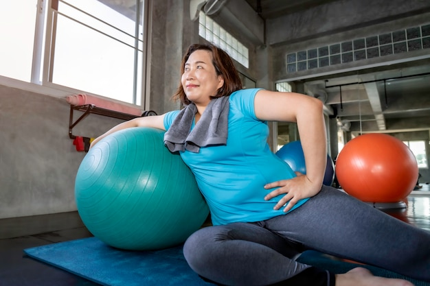 Mulher gorda sênior asiática fazendo exercícios de ioga no ginásio de fitness.