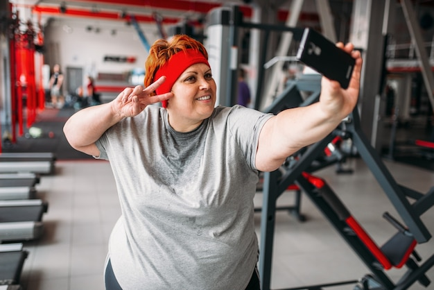 Mulher gorda suada faz selfie contra máquinas de exercício no ginásio. queima de calorias, mulher obesa em clube esportivo