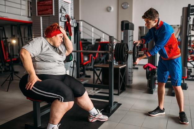 Mulher gorda usando barra, treinando com instrutor