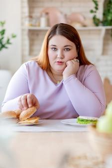 Mulher gordinha e infeliz segurando a bochecha enquanto come um hambúrguer