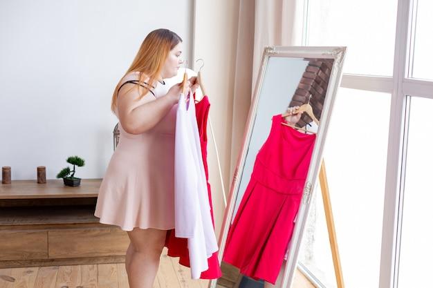 Mulher gordinha e simpática decidindo que vestido usar enquanto quer parecer elegante