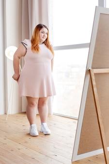 Mulher gordinha e simpática em frente ao espelho enquanto experimenta um vestido novo