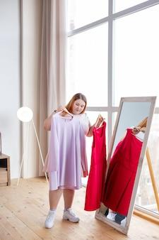 Mulher gordinha e simpática em frente ao espelho segurando dois cabides com vestidos