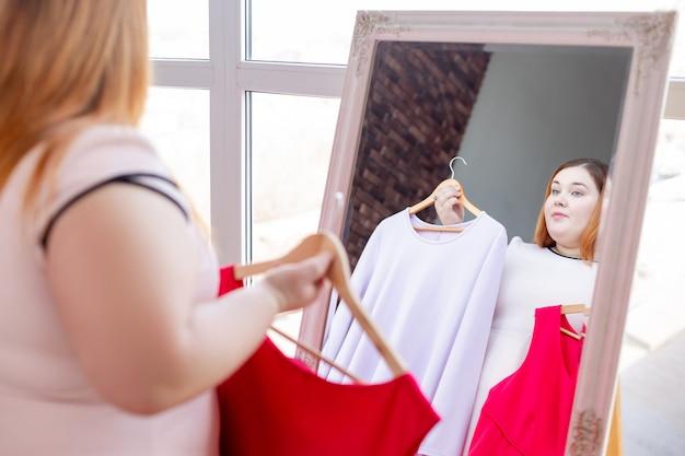 Mulher gordinha simpática olhando para seu reflexo enquanto escolhe um vestido para ela
