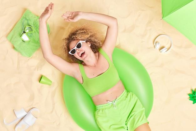 Mulher gosta de dia quente de verão na praia mantém os braços levantados poses na natação inflada usa top verde de óculos de sol e shorts encontra-se no sol tem um bom descanso.
