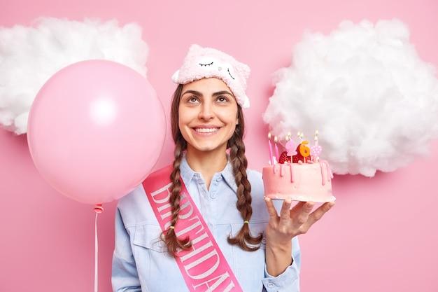 Mulher gosta de festa de aniversário segura bolo delicioso e balão inflado concentrado acima, vestida casualmente, expressa emoções felizes isoladas em rosa