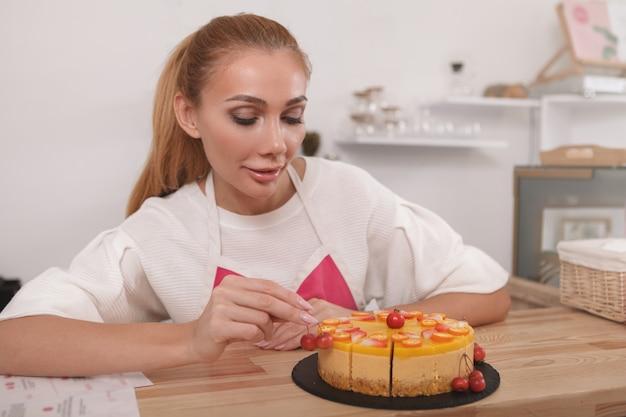 Mulher gostando de trabalhar em seu café decorando um saboroso bolo vegan cru fresco