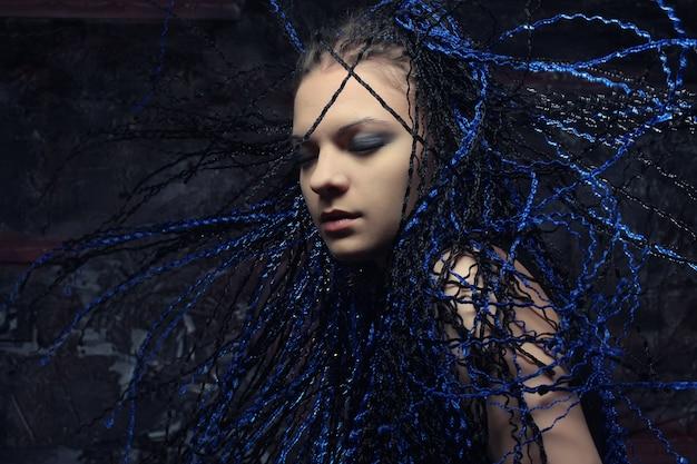 Mulher gótica com dreadlocks azuis.
