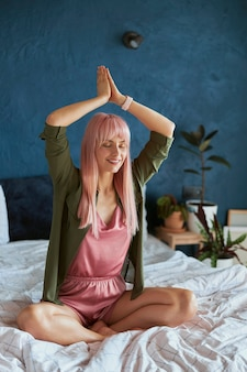 Mulher graciosa com cabelos coloridos meditando de mãos dadas em namaste acima da cabeça na cama