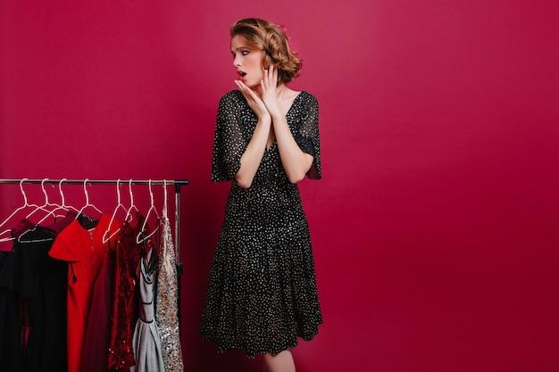 Mulher graciosa com expressão preocupada no rosto escolhendo roupa para encontro romântico