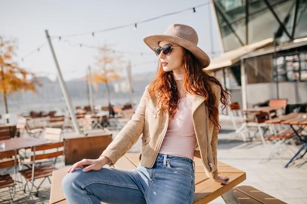 Mulher graciosa com longos cabelos ruivos olhando ao redor em um café ao ar livre no fim de semana de outono