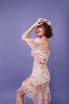 Mulher graciosa com pele pálida dançando. lindo modelo feminino em um vestido de primavera romântico, olhando por cima do ombro.
