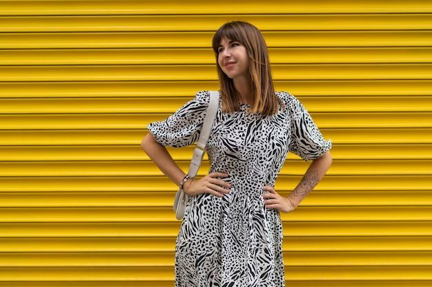 Mulher graciosa com tatuagem na mão, posando sobre muralha urbana amarela.