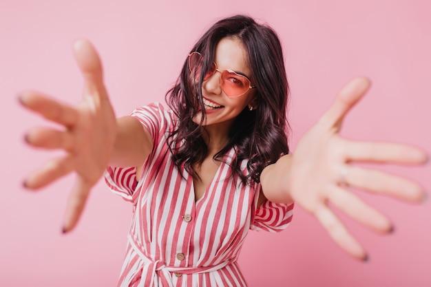 Mulher graciosa de cabelos escuros em óculos de sol rosa sorrindo. foto de uma senhora europeia encantadora em roupa listrada isolada.