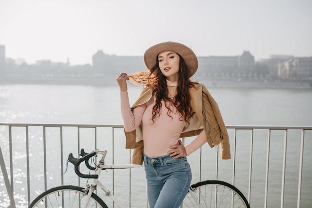 Mulher graciosa e fofa brincando com seu cabelo ruivo ao lado de uma bicicleta