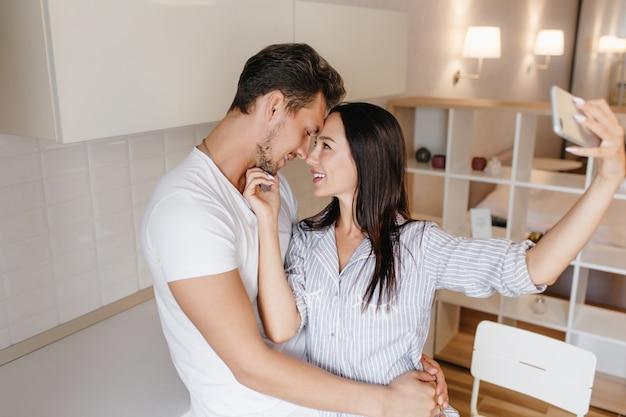 Mulher graciosa em camisa masculina brincando com o namorado no fim de semana e fazendo selfie