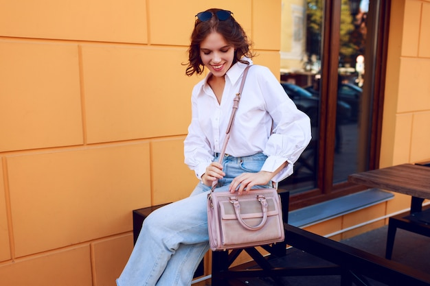 Mulher graciosa em roupa casual, sentado perto de café moderno com paredes amarelas. olhar na moda. humor positivo.