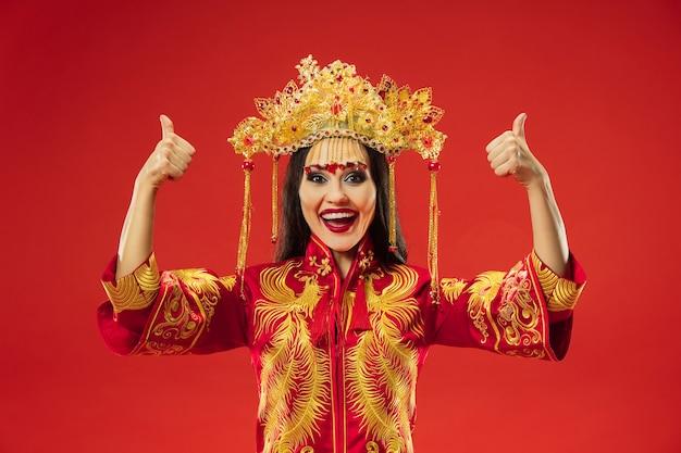 Mulher graciosa tradicional chinesa em estúdio sobre fundo vermelho. linda garota vestindo traje nacional. ano novo chinês, elegância, graça, artista, performance, dança, atriz, conceito de emoções