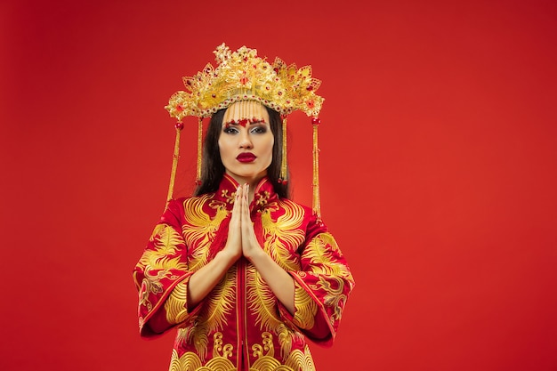 Mulher graciosa tradicional chinesa em estúdio sobre fundo vermelho. linda garota vestindo traje nacional. ano novo chinês, elegância, graça, artista, performance, dança, atriz, conceito de vestido