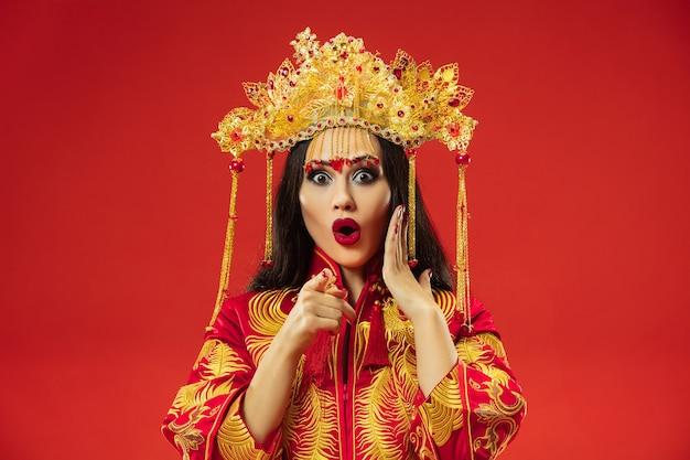 Mulher graciosa tradicional chinesa no estúdio sobre o vermelho.