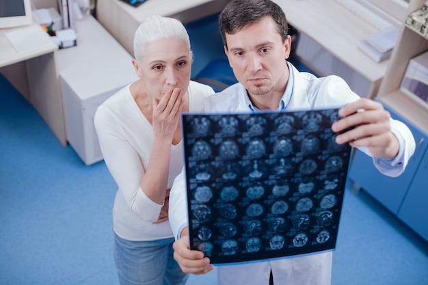 Mulher gravemente chocada e infeliz olhando para as imagens de raio-x do cérebro e cobrindo a boca enquanto fica surpresa com o diagnóstico
