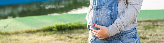 Mulher grávida abraçando a barriga perto do ar livre